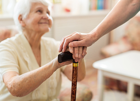 Nurse places a hand atop the hands of an elderly lady holding a walking stick