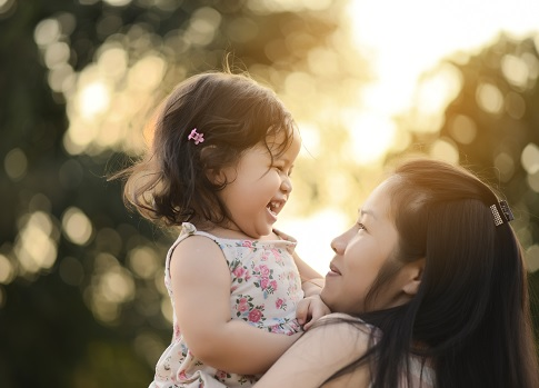 Smiling mother holds laughing little girl while standing in park
