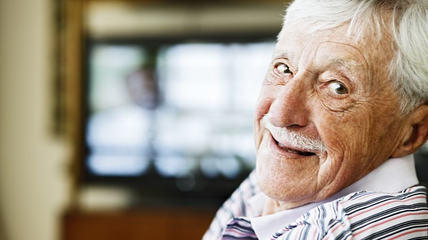 A smiling older gentleman peers over his shoulder at the camera