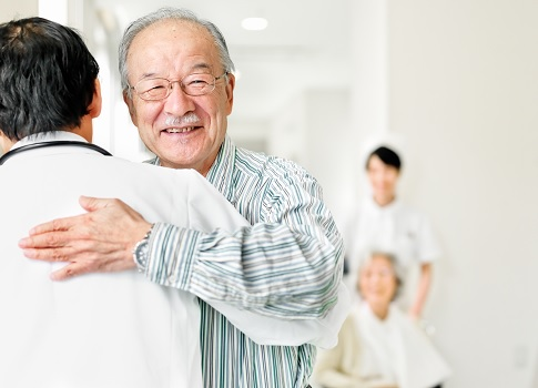 Smiling older man hugs his physician