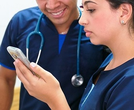 Two healthcare professionals look at a mobile device