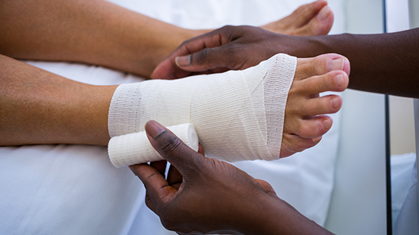 A nurse bandaging a wound on a patient's foot