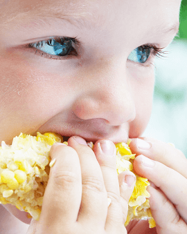 adorable-3-years-old-child-eating-sweet-corn