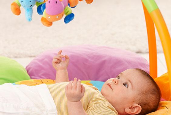 طفل مستلقي ويلعب على سجادة الالعاب