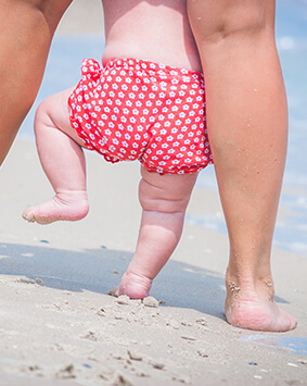 callout-mother-and-baby-feet-walking-on-a-sand-beach