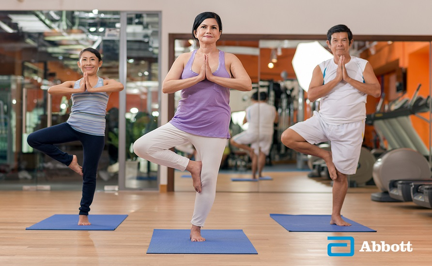 Healthy adults in yoga class training their strength and balance.