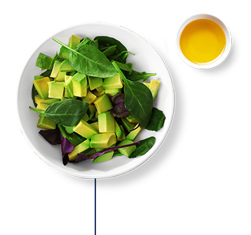 A mixed green salad with avocado, olive oil, and lime juice