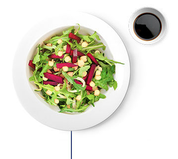 Salad with chickpeas, leafy greens, cucumbers, beets, & side dressing