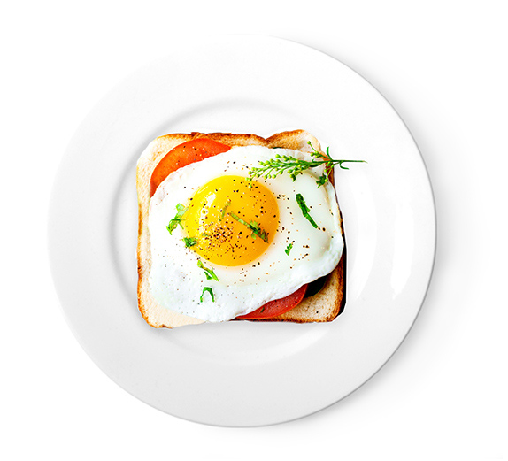 Breakfast sandwich with tomato and a sunny side up egg on top