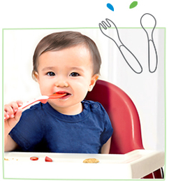 Asian baby chewing on a spoon in a high chair