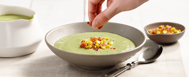 Avocado soup made with Ensure® Regular garnished with corn and bacon