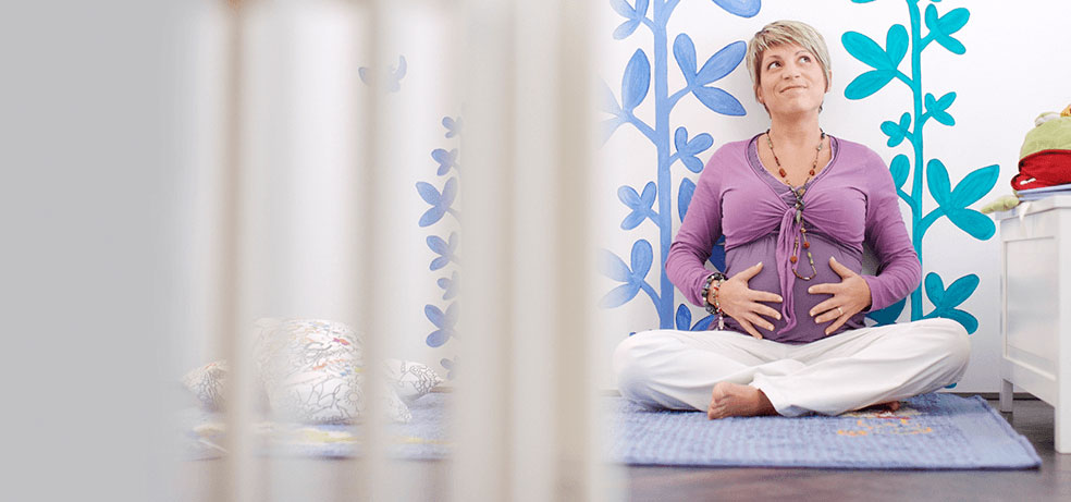 Pregnant woman holding her stomach looking upwards while sitting on a mat