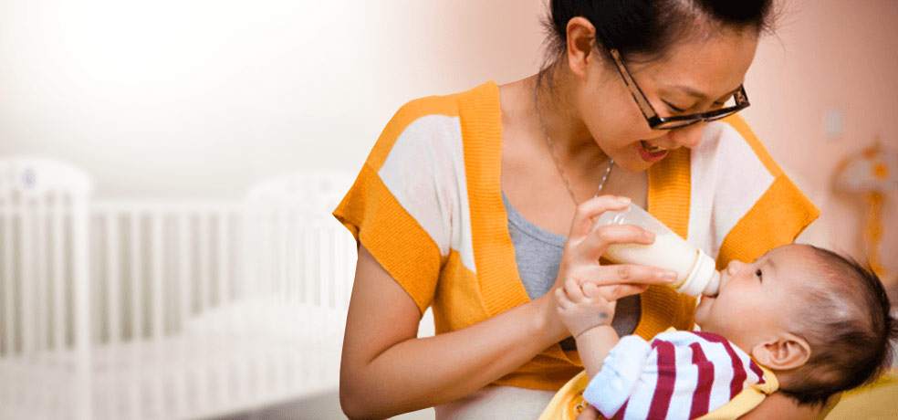 An Asian mother feeding her baby with a milk bottle in a room