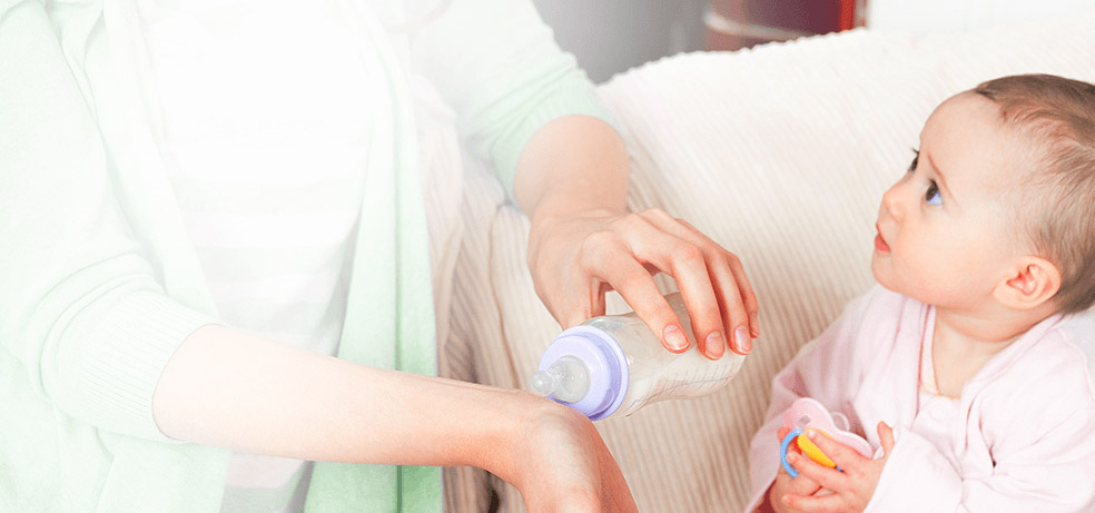 An infant girl watching her mom test the baby's bottle temperature on her wrist