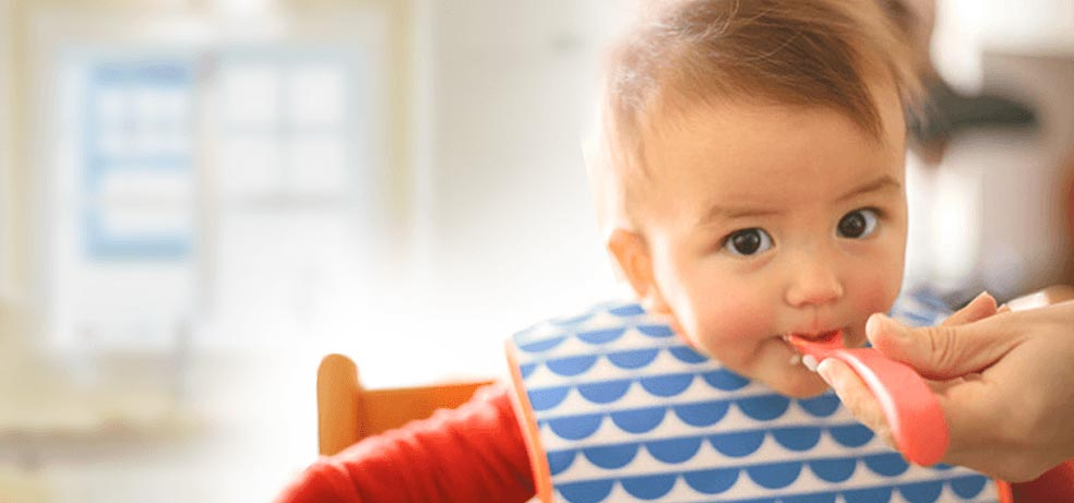 A baby girl with a bib eating from a red plastic spoon