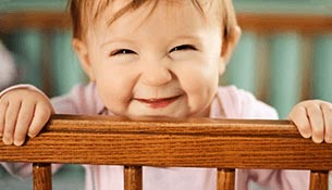 A six month old girl smiling while inside a crib