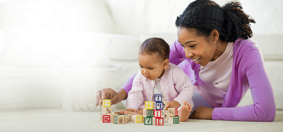 Older Premature Baby Girl Playing with Toy Blocks along with Her Mother
