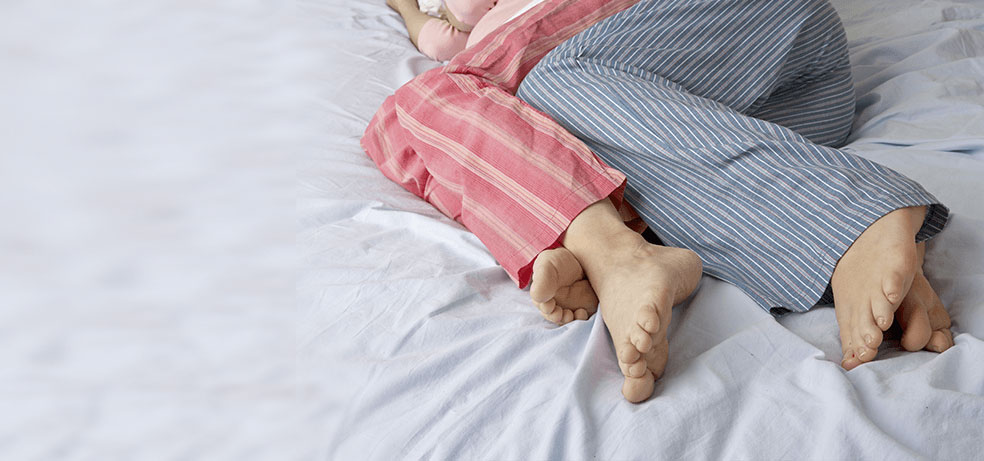 The legs of a couple in pajamas while on the bed
