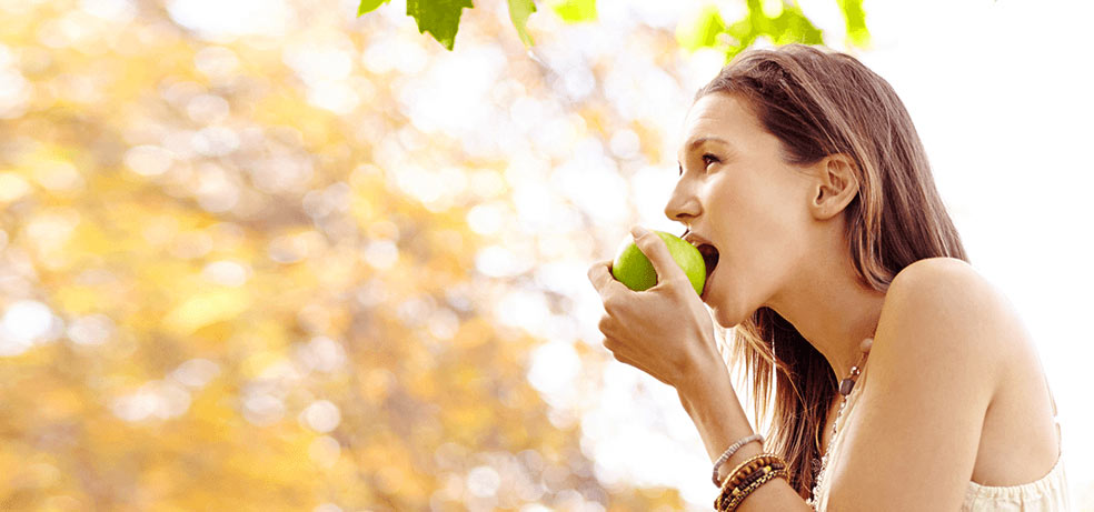 A woman about to eat a green apple while outside