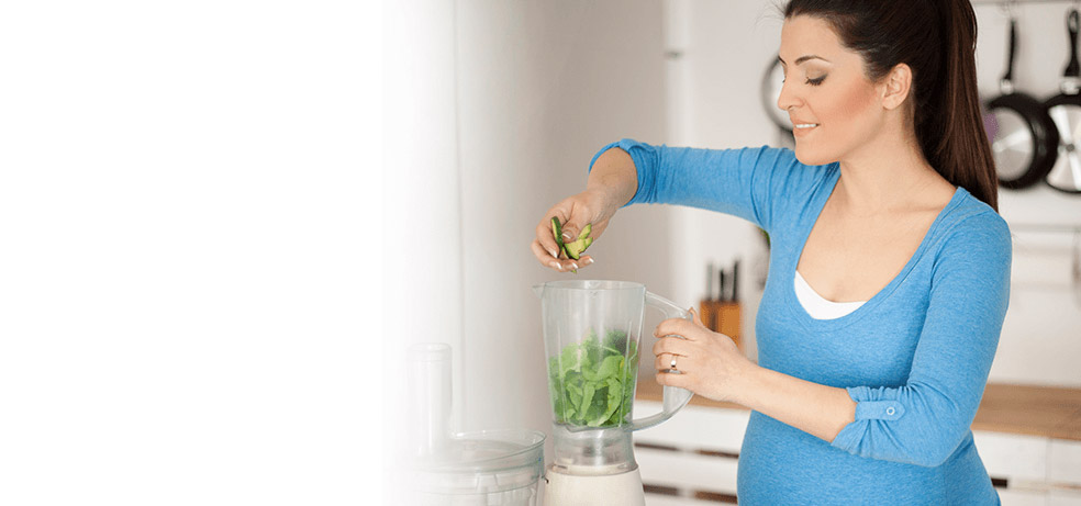 A pregnant woman in the kitchen placing vegetables in the blender