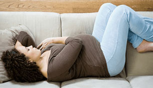 An expectant mother lying down on a couch