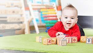 An infant on his stomach playing with baby letter cubes