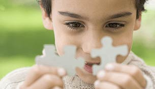 A male child holding two puzzle pieces close to each other